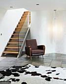 Zeitgenössische Treppe in puristischem Wohnraum mit Kuhfell auf Natursteinboden