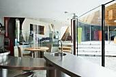 Offene Küche und Essplatz im Designerstil entlang gebogener Fensterfront mit Blick auf höher gelegenen Wohnraum-Ebene