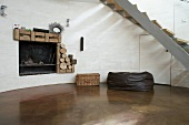 Rounded wall with open fireplace and polished concrete floor beneath staircase with curved steel stringer