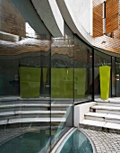 Terrace of contemporary house - reflections in curved glass facade and elliptical glass panel to light cellar