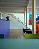 Kitchen counter, seating and modern art in clear, bold colours in living space with steel pillars and corrugated metal ceiling