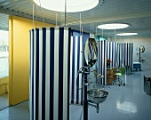 Cool, maritime atmosphere in unusual bathroom with bullseye windows in ceiling and blue and white striped screens