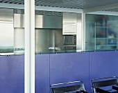 Lavender-coloured kitchen counter and black Bauhaus chairs in front of stainless steel kitchen units
