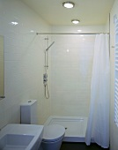 Compact configuration in a small space - cream tiles and white, modern bathroom furnishings with maritime ceiling lights