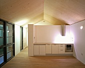 Open-plan attic room with simple kitchen unit in front of half-height partition under spotlight