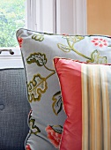 Shiny, striped and floral scatter cushions on sofa with grey, woven fabric cover