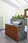 Modern bathroom with glass roof and grey tiles; wooden doors on central washstand island with integrated planter