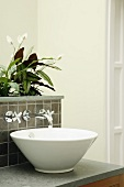 Wash basin with wall-mounted taps and integrated planter with flowering zantedeschia