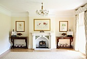 Traditional living room with chandelier and ornamental fireplace between antique console tables
