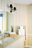 Cream, traditional-style bathroom with striped wallpaper, lamps with lampshades and marble washstand