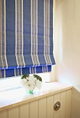 Blue striped Roman blind and small posy above white-painted, wooden wall panel