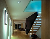 Floating staircase between wall and dark stringer element with indirect light through glass ceiling