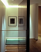 View from glass balustrade of framed artwork and glass floor on landing of open wooden staircase
