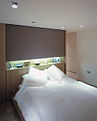 Double bed with snow-white linen in front of wall unit with indirect lighting and knick-knacks