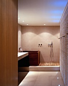 Purist ensuite bathroom with wall-mounted fittings on matte stone tiles, wooden bathtub and shower area with wooden slatted floor