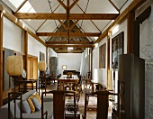 Long, narrow living-dining room with collection of wooden chairs and balloon lamps in historic building with new roof timbers