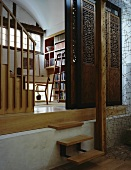 Sliding wall made from antique, carved wooden elements in front of library and delicate, sculptural wire partition