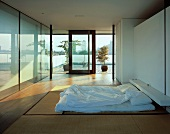 Modern, Japanese-style bedroom with futon on tatami mats and view of Japanese terrace garden and cityscape