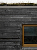 Weathered wooden cladding on ecological house with turf roof