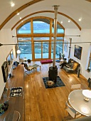 Open-plan living space seen from above with central wood-burning stove below arched ceiling and glass wall with view of wooden terrace