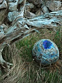 Blue-glazed ceramic sphere with ribbon of text lying in grass next to gnarled root wood