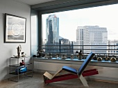 Retro-style, upholstered wooden lounger and shelves in front of panoramic window with view of Berlin skyscrapers and decorated windowsill