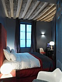 Double bed with red header in French hotel room with dark decor and exposed ceiling beams