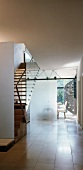Frosted glass partition between flight of wooden stairs and perforated sheet metal spiral staircase in contemporary house