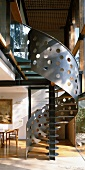 Gallery in living space - sheet metal with irregular punched holes forms balustrade of modern spiral staircase