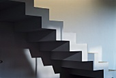 Pattern of light and shade on cubic, zigzag staircase without balustrade