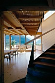 Contemporary wooden house - staircase to gallery in open-plan, light living space with view of mountains
