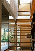 Pared-down stair structure with open treads fixed on glass wall in open-plan living space of modern wooden house