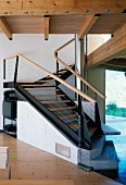 Spiral wood and steel staircase with sloping elements and stone bottom steps in contemporary, Tyrolean wooden house