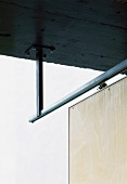 Steel-framed wooden door on rail suspended from concrete ceiling against the light