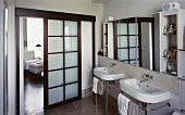 Bathroom with washstands on metal frames and open sliding wooden door with panels of opaque glass