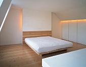 Simple bedroom with mattress on wooden platform in white attic room with indirect lighting