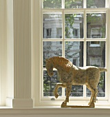 Horse sculpture on window sill of lattice window