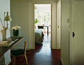 Hallway with seat & open door to bedroom