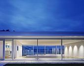 Modernes Wohnhaus mit Glasfronten im Abendlicht