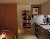 A modern living room-cum-kitchen with a view of a neighbouring room and a bookshelf