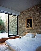 A modern bedroom with brick walls, an antique painting in a gold frame and view into a courtyard