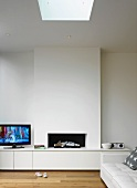 A modern fireplace with an integrated sideboard in a pure white room