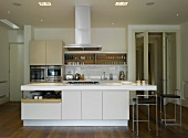A kitchen in an open-plan living room with an island counter and a central extractor hood