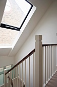 A stair way in an attic with a large skylight