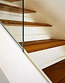 White metal staircase with wooden treads and glass balustrade