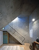 A bedroom with concrete wall and a slanted ceiling and a flight of concrete steps