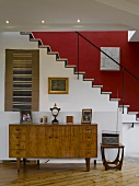 Retro-style cabinet in front of staircase with red-painted wall