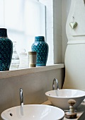 Two sinks & two blue vases on windowsill