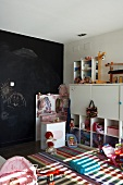 Children's drawings on black wall behind white children's furniture, colourful rug and girls' and boys' toys