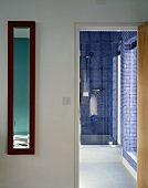 Foyer with open door and view of shower cubicle with blue mosaic tiles in bathroom
